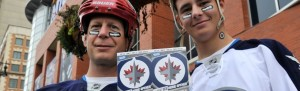 Photo unceremoniously borrowed from the Winnipeg Sun: Winnipeg Jets fans Nelson (right) and Doug Quara show off their tickets before the NHL Winnipeg Jets inaugural game against the Montreal Canadiens in Winnipeg, October 9, 2011. REUTERS/Fred Greenslade