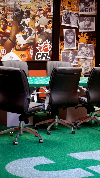 The BC Lions conference room features a table painted like a CFL football field, life-sized photos of Grey Cup winners and assorted team legends, and — wait for it — actual Astroturf flooring painted like centre field. Photo by Jason Kurylo for Pucked in the Head.