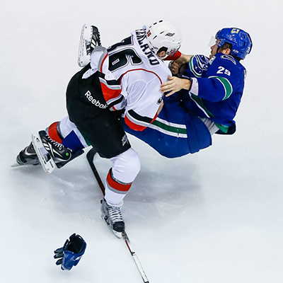 Michael Ferland of the Abbotsford Heat knocks Utica Comets defenseman Kent Huskins off his feet with a single punch in AHL action. Clint Trahan photo courtesy of the Abbotsford Heat.
