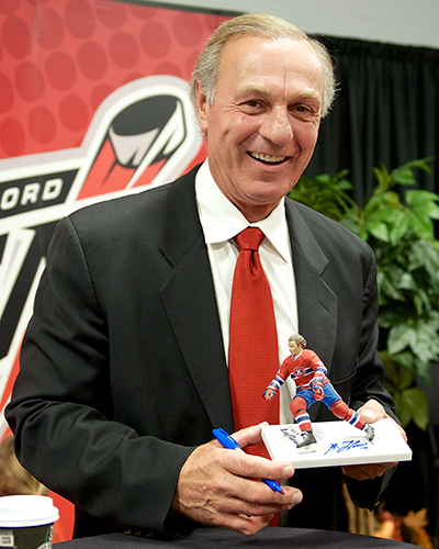 Hockey Hall of Famer Guy Lafleur poses with his Spawn Toys likeness during the Abbotsford Heat home opener Friday night. Photo by Jason Kurylo for Pucked in the Head.