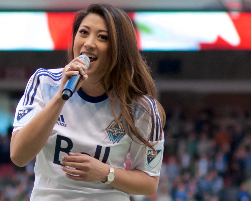 Marie Hui sings the national anthem prior to the Vancouver Whitecaps season opener. Sadly, the home team lost their 2015 home opener to the dirty, rotten, stinkin' doughbugs of TFC 3-1. Photo by Jason Kurylo for Pucked in the Head.
