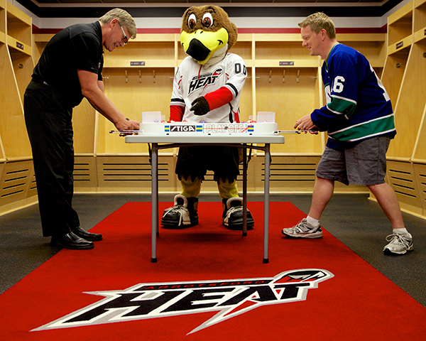 Ryan Walter (left) battles Jason Kurylo for table hockey supremacy as Hawkey looks on in the Abbotsford Heat locker room. Photo by Clint Trahan for Pucked in the Head.