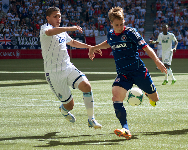 Johnny Leveron keeps a close eye on Chris Rolfe, who was unable to capitalize on an early handball missed by officials. Vancouver Whitecaps FC defeated Chicago Fire 3-1 on 14 July 2013 on the strength of two goals by Camilo de Sanvezzo. Photo by Jason Kurylo for Pucked in the Head.