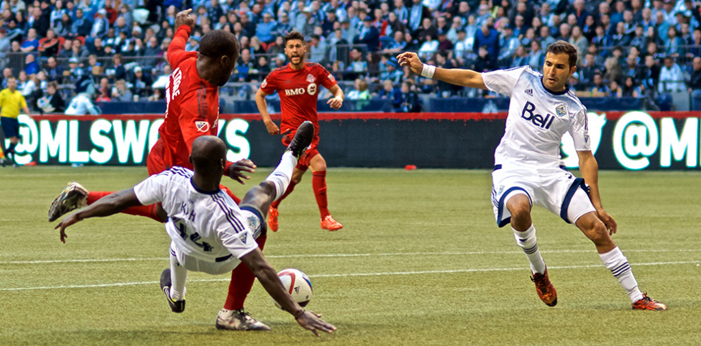 Pa-Modou Kah was called for a late PK after taking down TFC striker Jozy Altidore. The Vancouver Whitecaps lost their 2015 home opener 3-1. Photo by Jason Kurylo for Pucked in the Head.